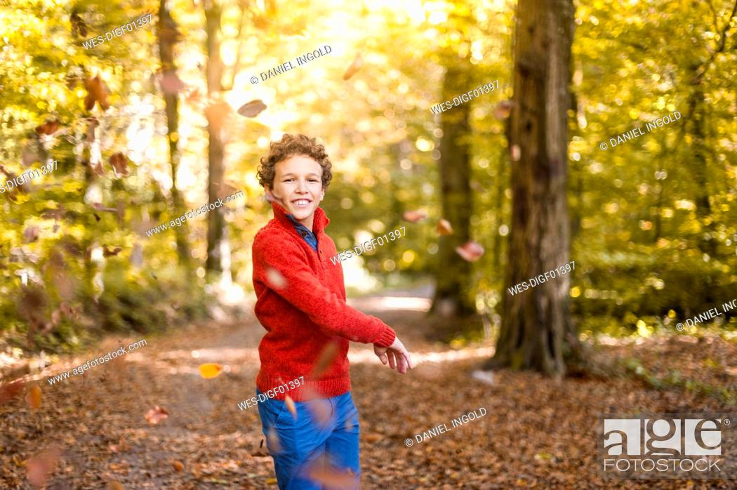 Stock Photo: Smiling boy throwing leaves in the air in the autumnal forest.