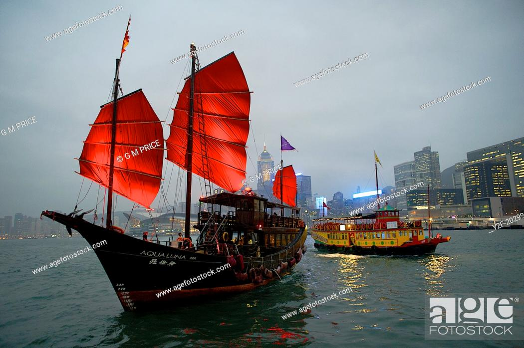 Imagen: Two boats pass each other at night on Victoria Harbour, Hong Kong - the iconic Aqua Luna with Red Sails and a Wing On Travel boat.