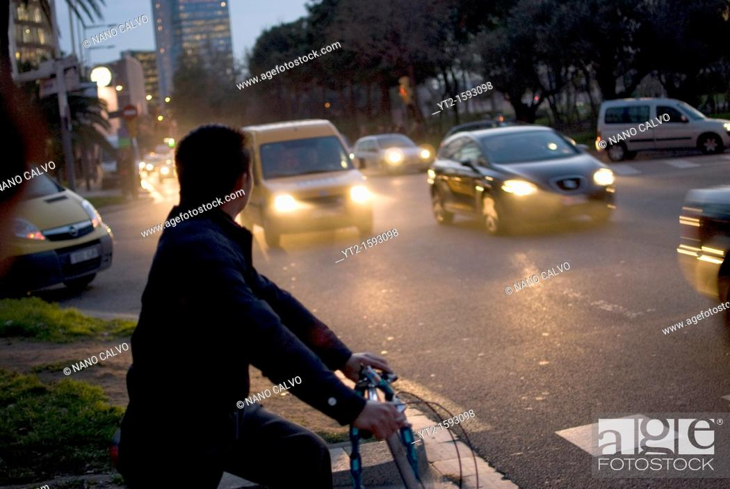 Stock Photo: Asian man in his bike, waiting to cross the road at night, Barcelona.