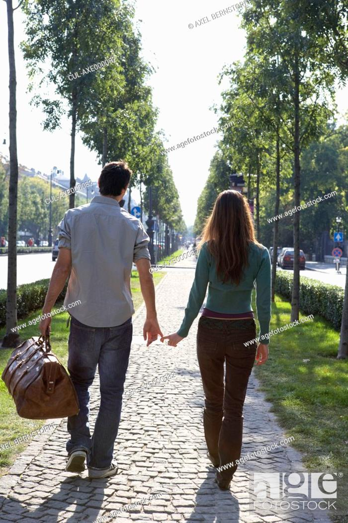 Stock Photo: Couple walking together with a large bag.
