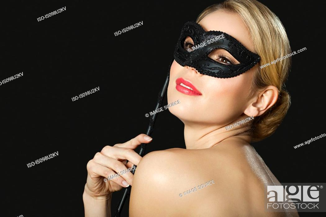 Stock Photo: Young blonde woman wearing with black mask.