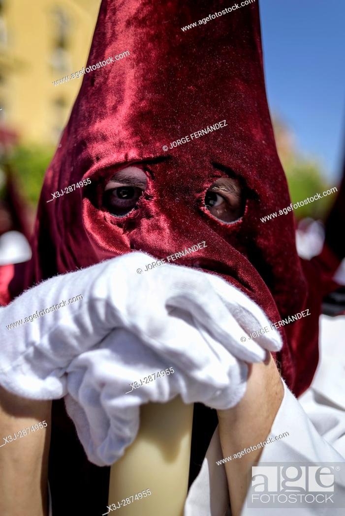 Stock Photo: Portrait of a Nazarene penitent with red hood and white robes participating in a procession .