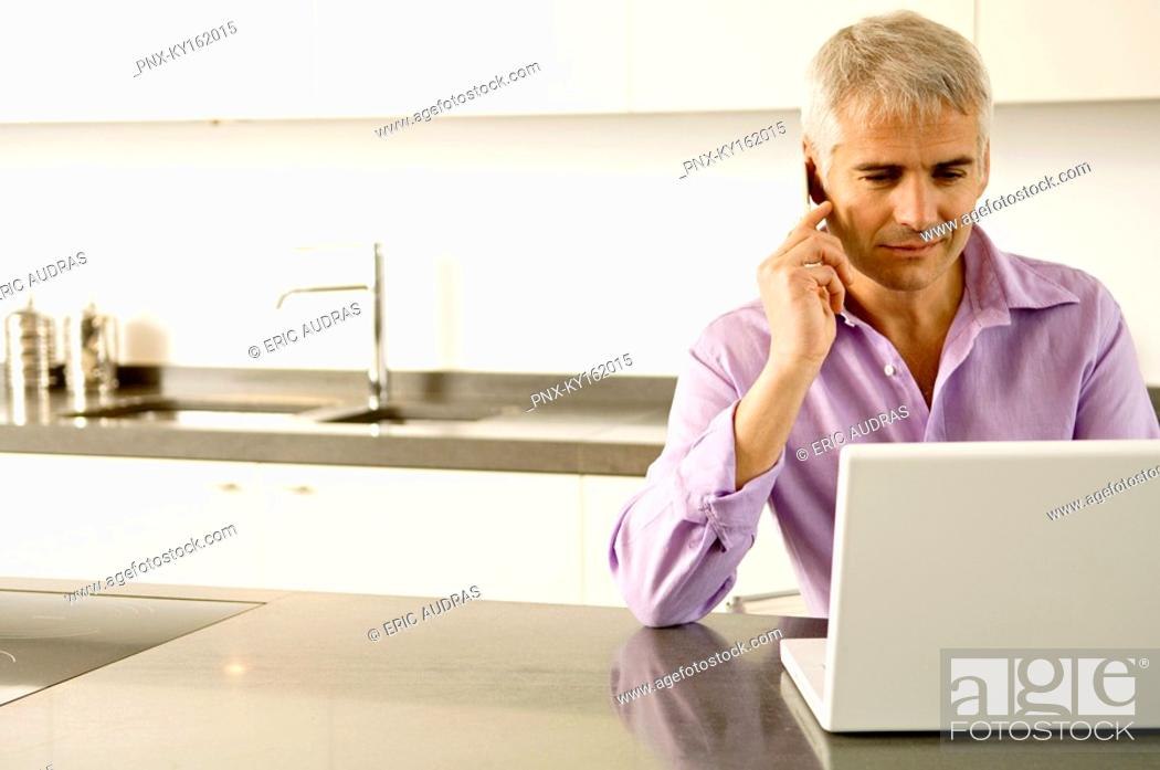 Stock Photo: Mature man working on a laptop while talking on a mobile phone.