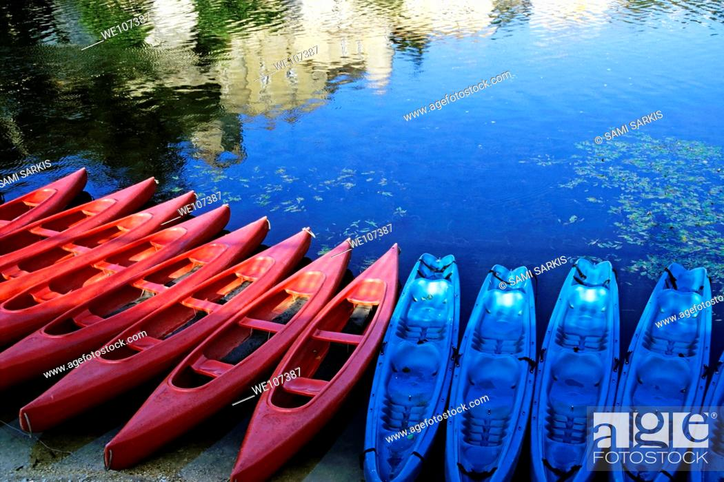 Stock Photo: Kayaks lined up along the Lot riverbank at sunset, Puy-l'Évêque, Lot, France.