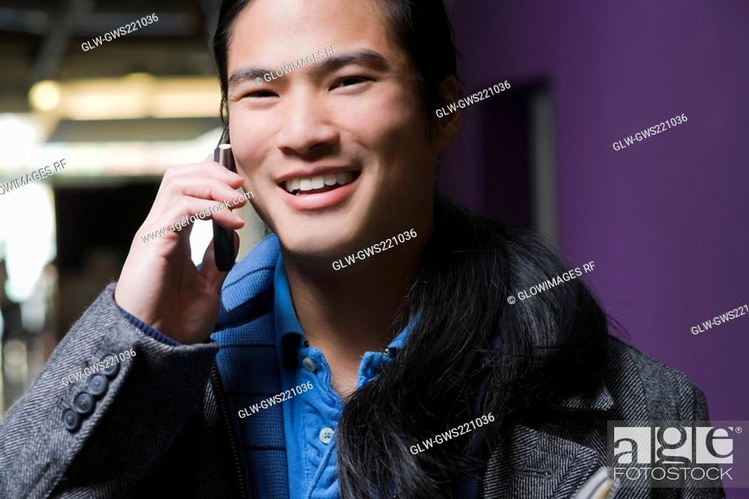 Stock Photo: Young man talking on a mobile phone and smiling.