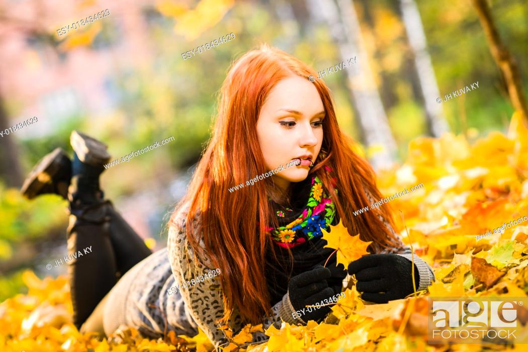 Stock Photo: Red-haired girl lying on park, maple leaves and colors of autumn.