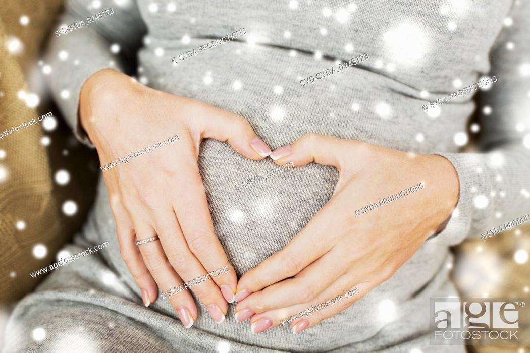 Stock Photo: pregnant woman making heart gesture on her belly.