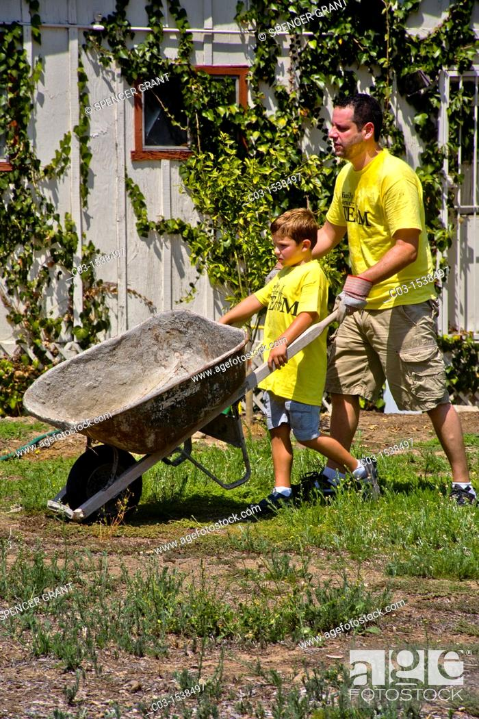 Father And Son Share The Task Of Pushing A Wheel Barrow At A