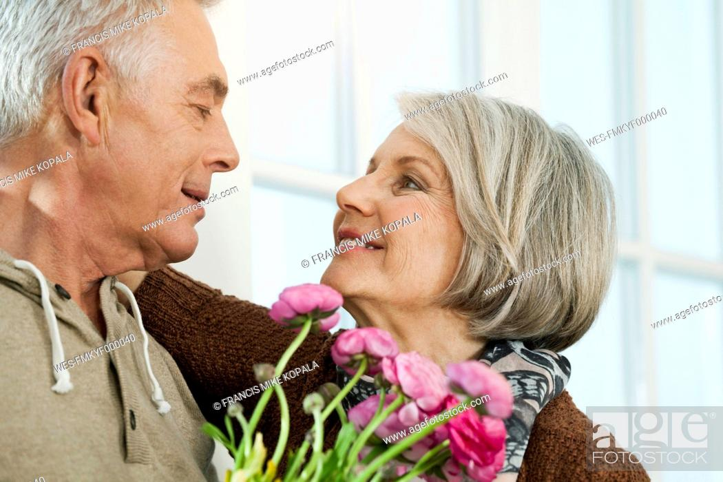 Stock Photo: Germany, Berlin, Senior couple looking at each other, smiling.