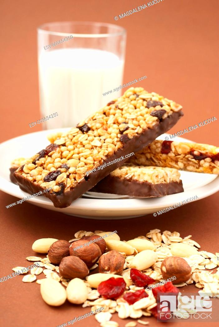 Photo de stock: Granola bar, almonds, nuts, dry cranberries, oat flakes and glass of milk.