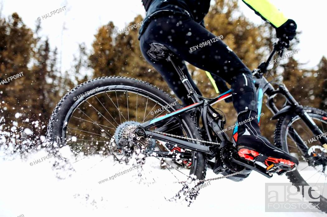 Imagen: A midsection of mountain biker riding in snow outdoors in winter.