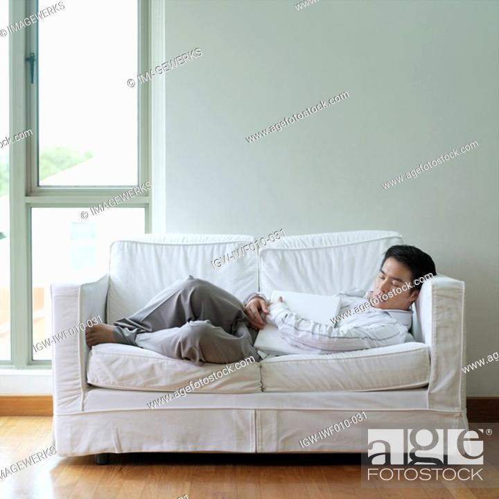Stock Photo: Side profile of a young man sleeping on a couch.