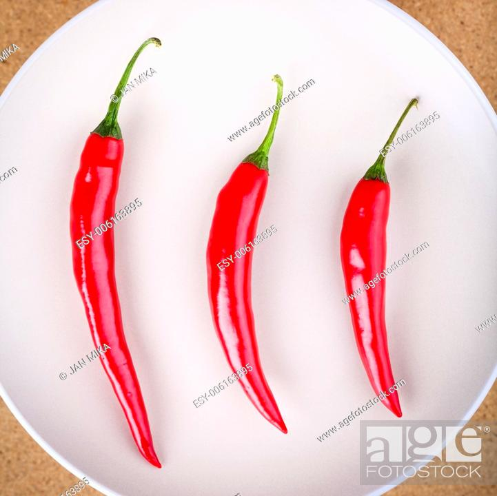 Stock Photo: Closeup of three fresh raw red hot chili peppers on plate.