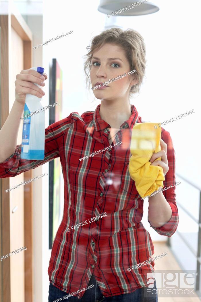 Stock Photo: Woman cleaning glass door.