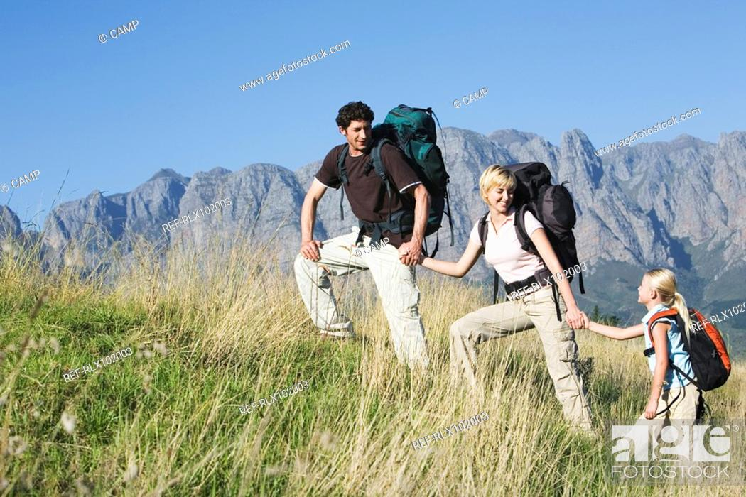 Stock Photo: Young couple with daughter hiking with backpack, mountains in background.