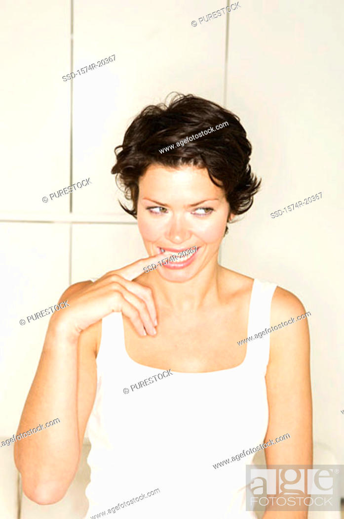 Stock Photo: Close-up of a young woman biting her finger.