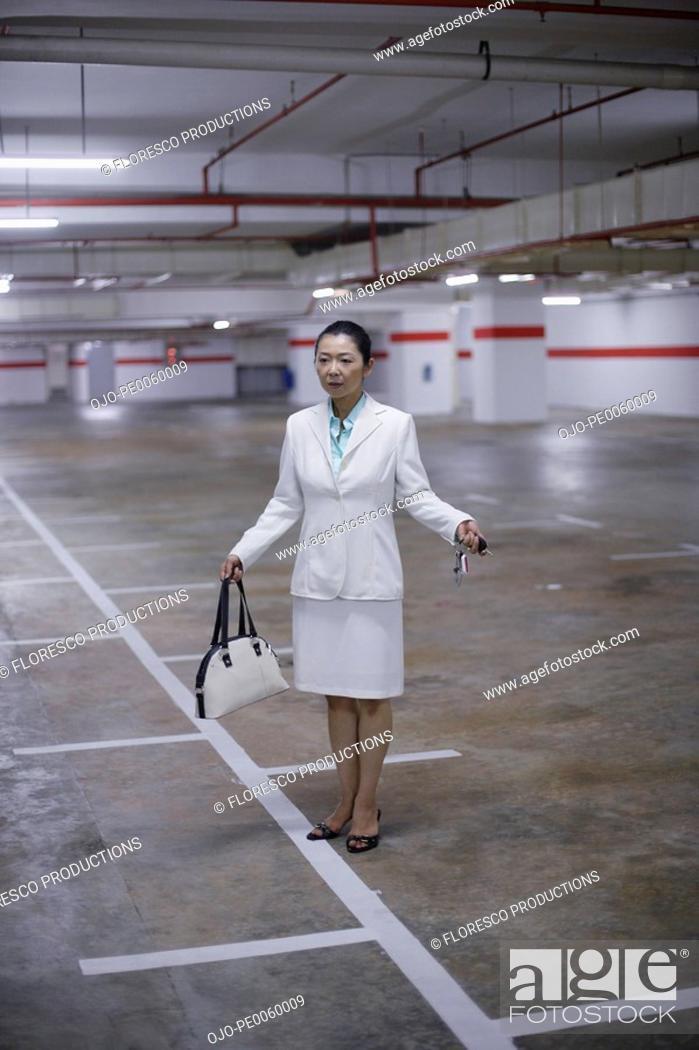 Stock Photo: Businesswoman in indoor parking garage looking for her car.