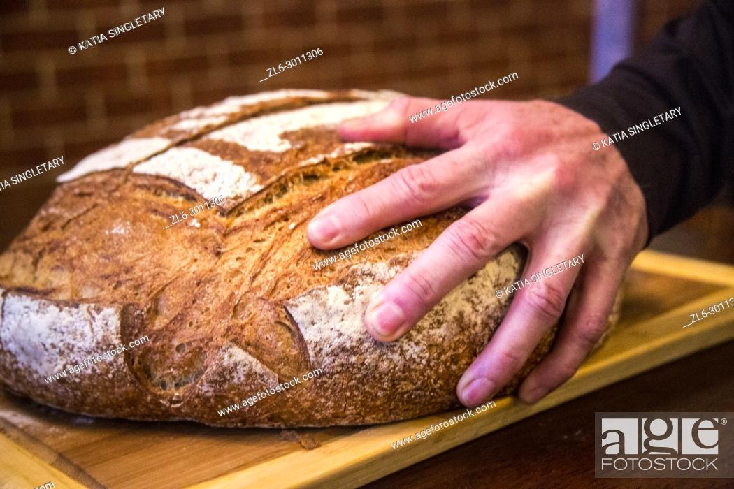 Stock Photo: Man with a black shirt cutting a round loaf of bread. We can see the long bread knife cutting the bread in half and pieces.