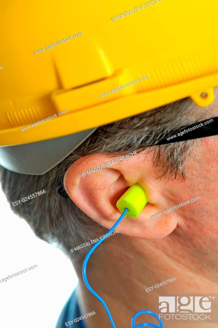 Stock Photo: yellow earplug into the ear.