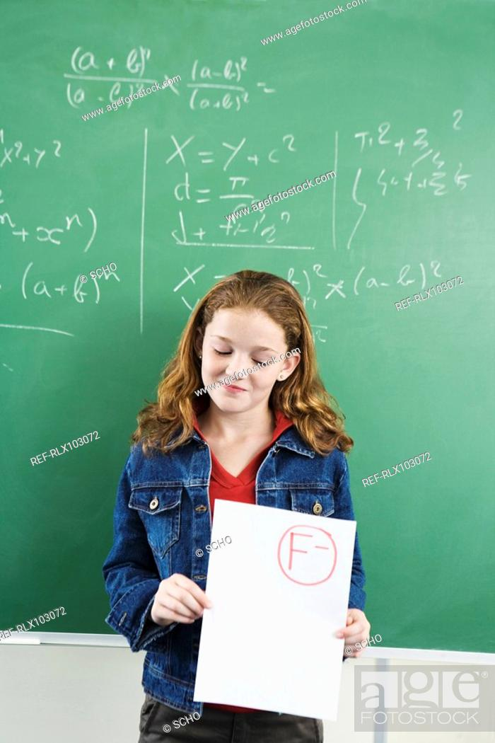 Stock Photo: School girl 10-13 in classroom standing at blackboard holding result paper.