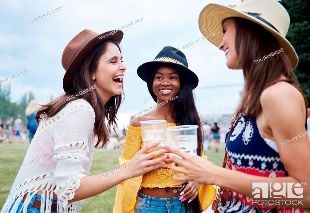 Stock Photo: Friends drinking in music festival.