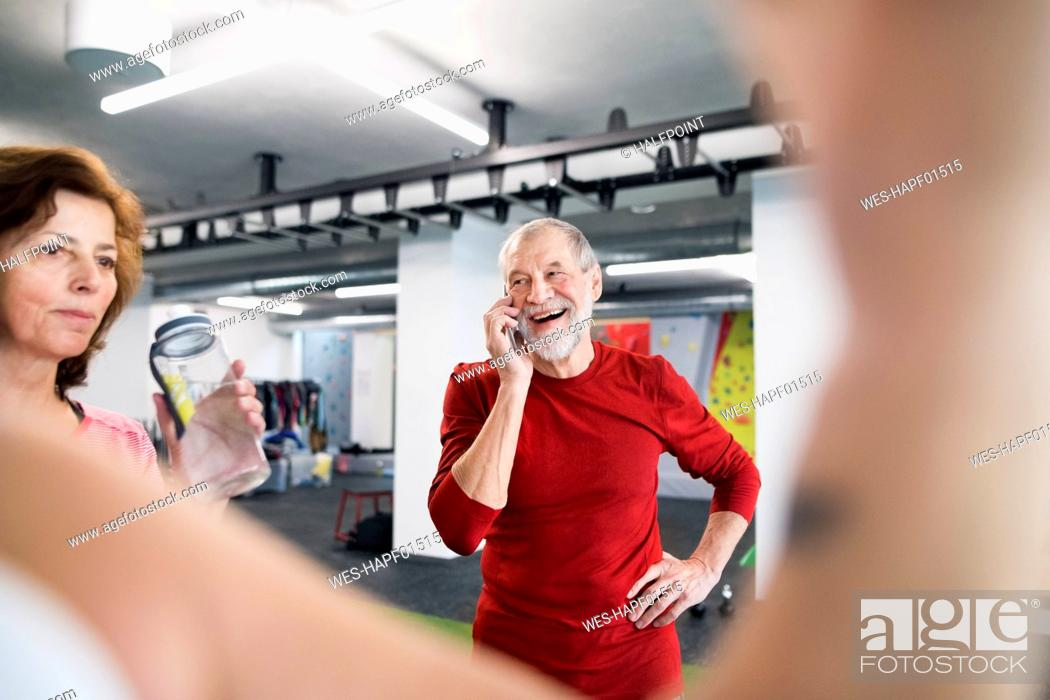 Stock Photo: Fit senior man with smart phone in gym.