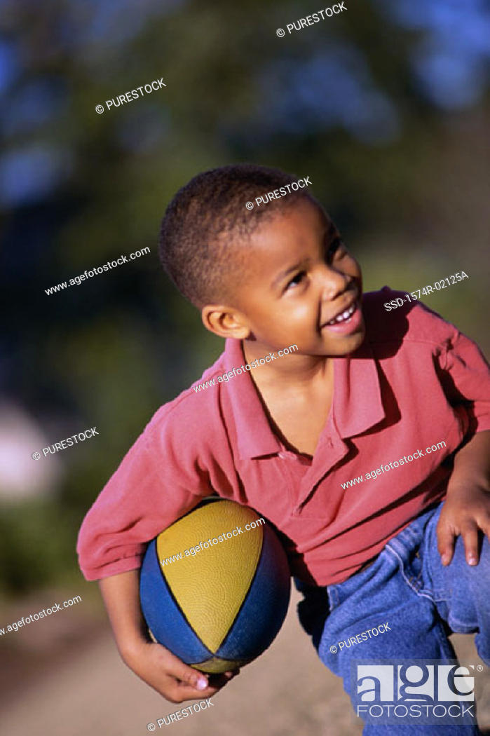 Stock Photo: Boy kneeling with a rugby ball.