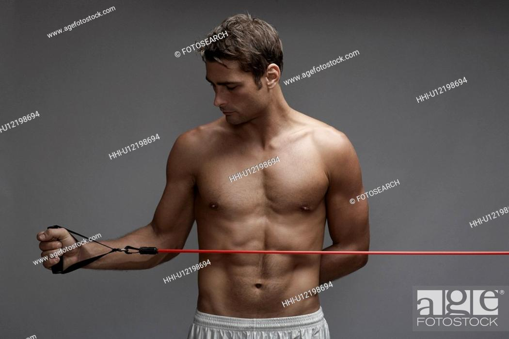 Stock Photo: Mid adult man weight training with cable.