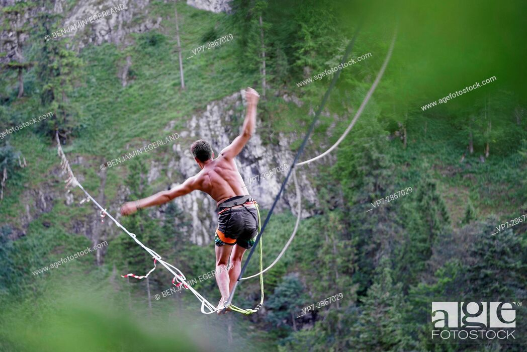 Imagen: Young outdoor sportsman balancing on slackline over valley in south of Germany, Bavaria, near border to Austria.
