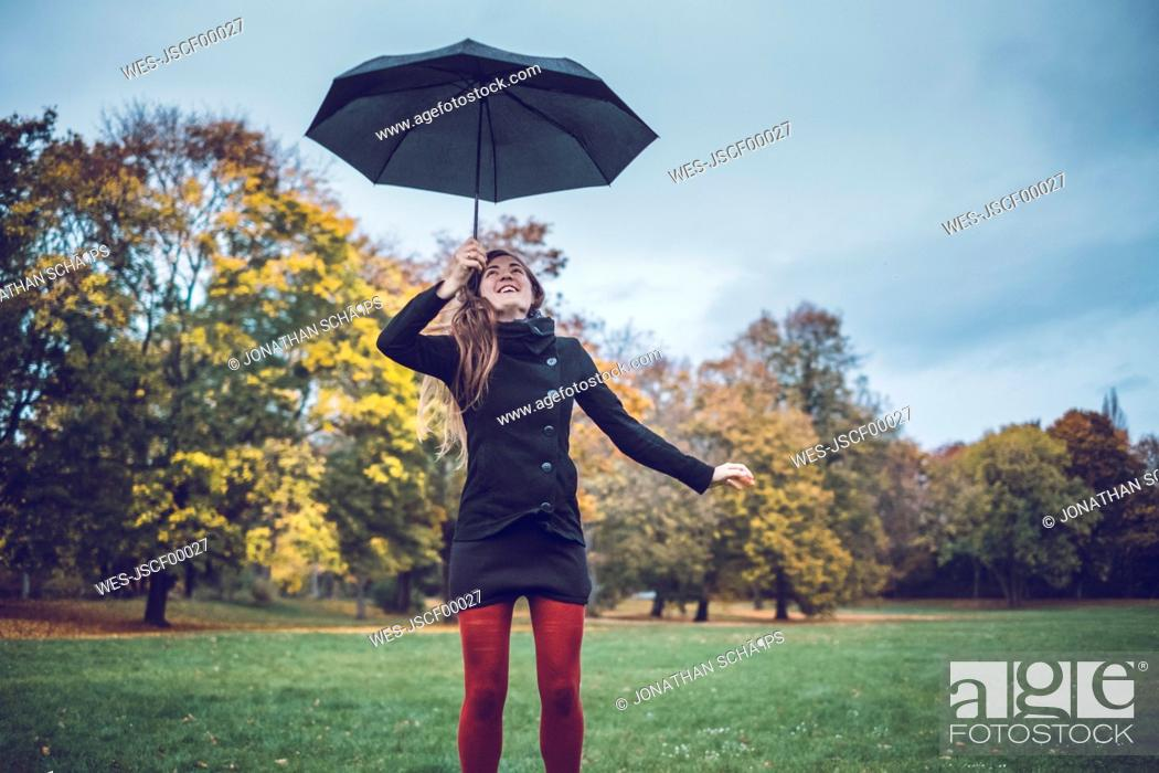 Stock Photo: Young woman with umbrella in autumnal park.