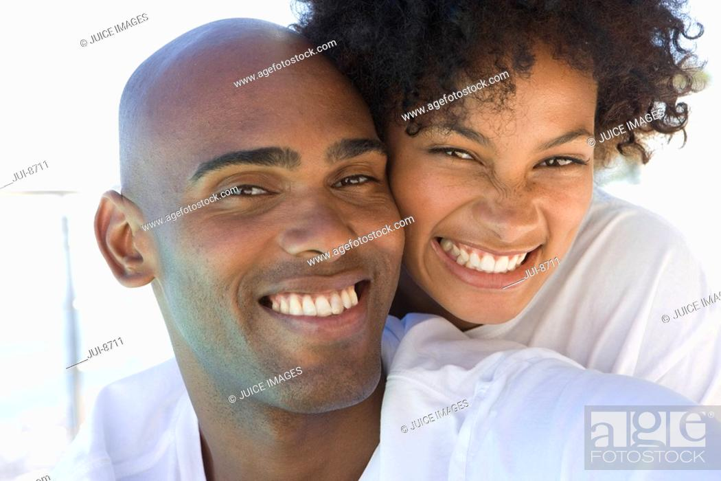 Stock Photo: Young couple embracing, smiling, portrait, close-up.