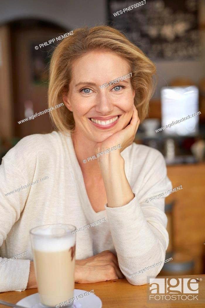 Stock Photo: Portrait of relaxed woman with Latte Macchiato in a coffee shop.