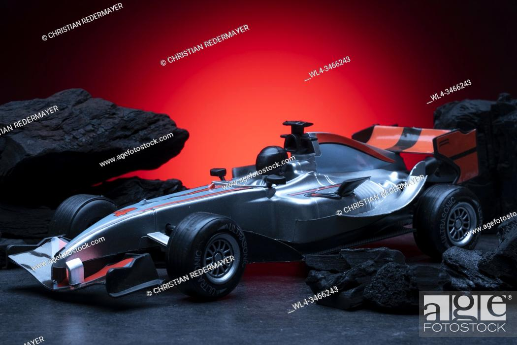 Stock Photo: Formula one toy car in between black coal.