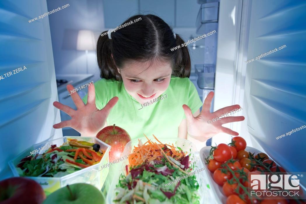 Stock Photo: Girl looks in the fridge.