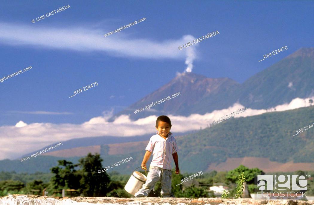 Stock Photo: Mayan boy and the Volcán de Fuego in background. Antigua Guatemala. Guatemala.