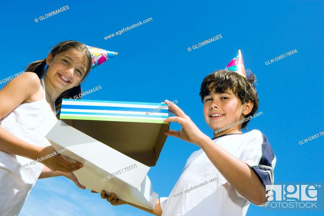 Stock Photo: Portrait of a girl giving a birthday present to her brother.
