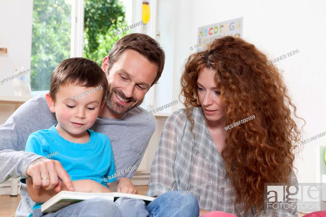 Stock Photo: Germany, Berlin, Family reading book at home.