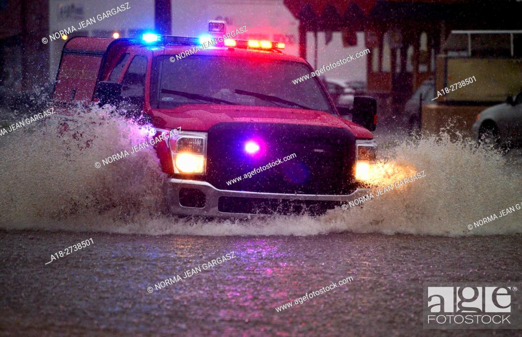 Stock Photo: An emergency services vehicle drives through flooded streets during a monsoon storm, Sonoran Desert, Tucson, Arizona, USA.