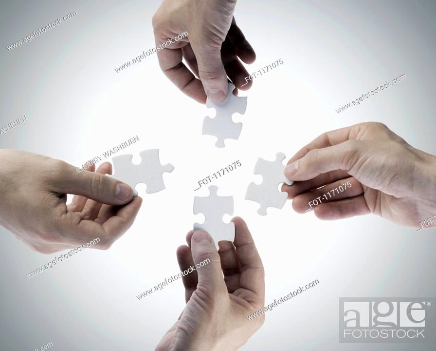 Stock Photo: Four hands holding jigsaw puzzle pieces, directly above.