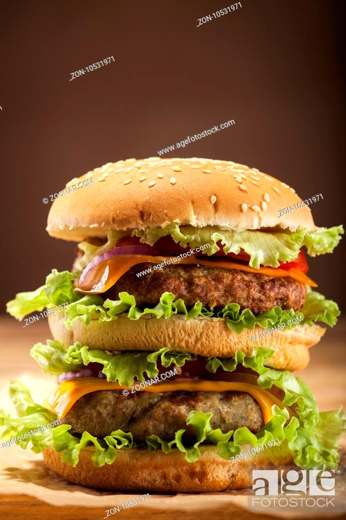 Stock Photo: Fresh delicious double burger with meatball, cheese, tomato, onion, french fries and lettuce on wooden table and brown background with copy space.