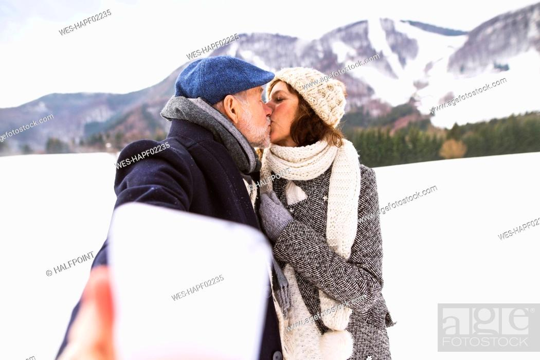 Stock Photo: Senior couple kissing in winter landscape while taking selfie with cell phone.