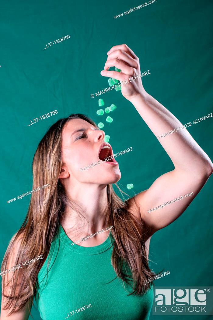 Stock Photo: Young woman in green dropping green candy pieces in her mouth.
