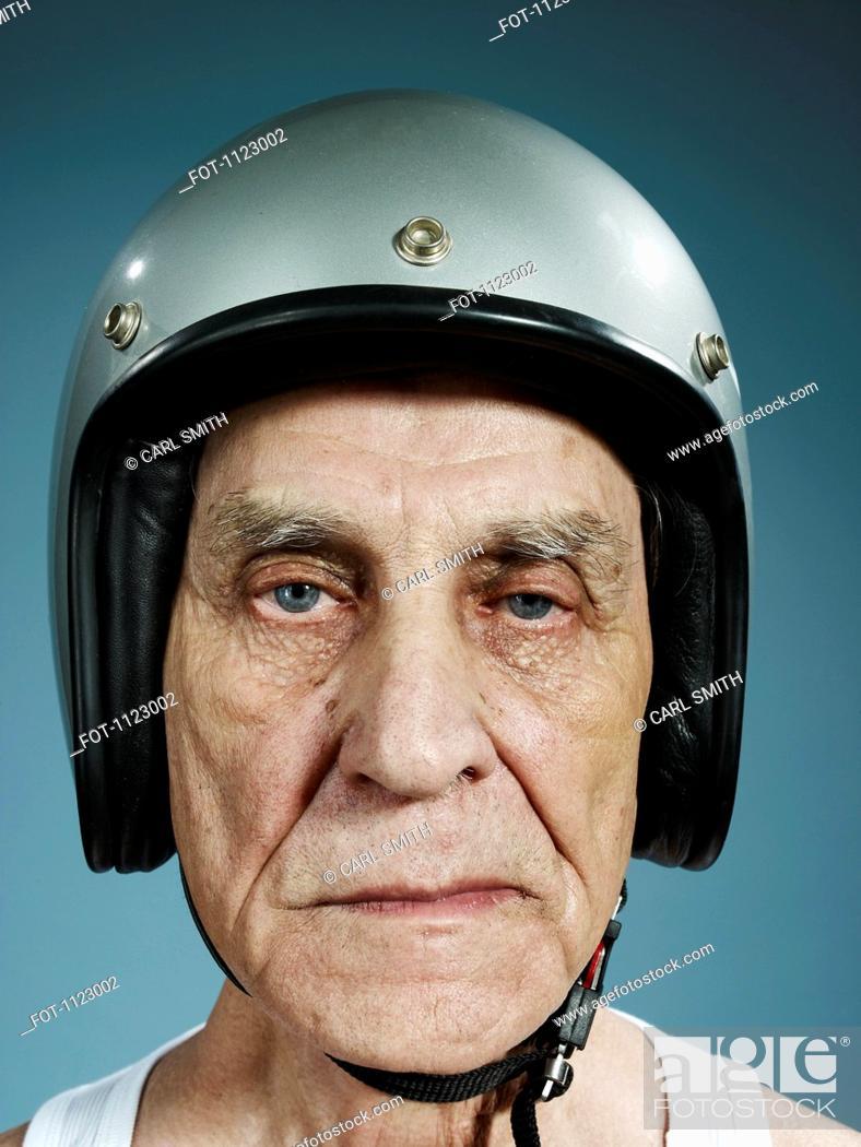 Stock Photo: A headshot of a frowning senior man wearing a crash helmet.