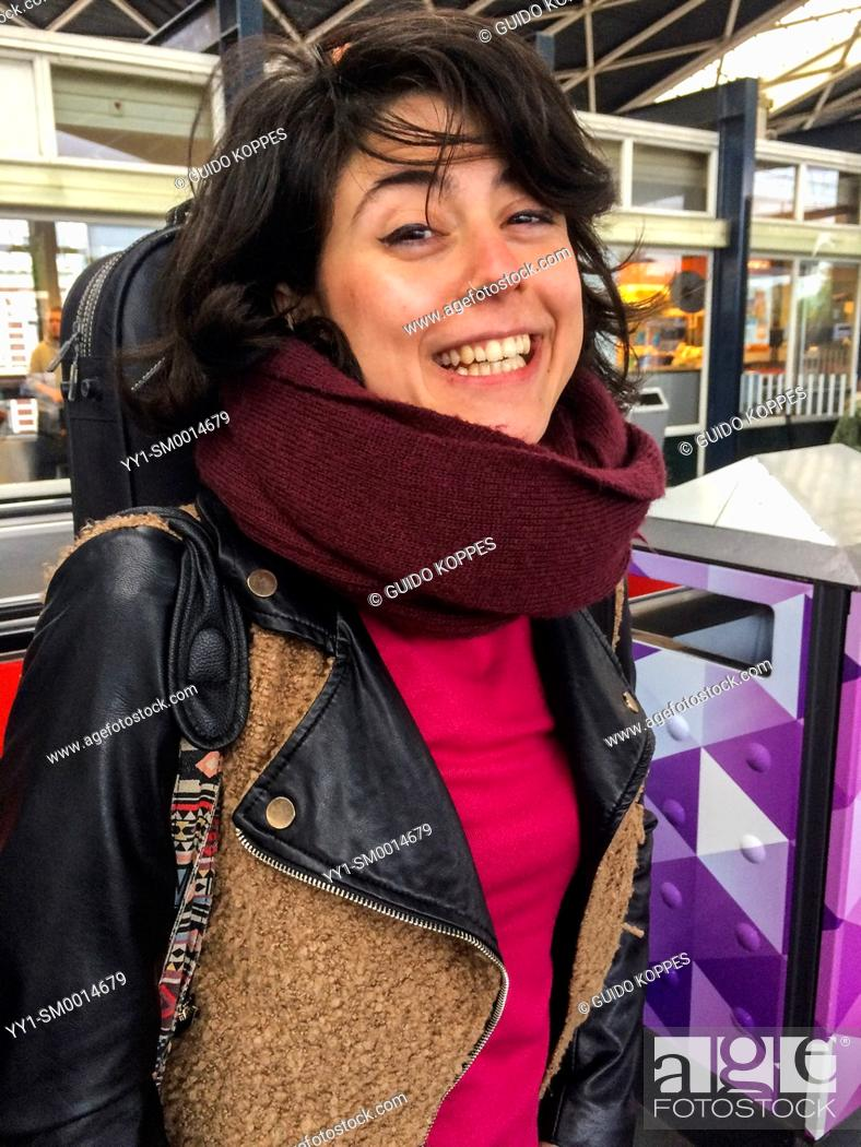 Stock Photo: Tilburg, Netherlands. Happy and smiling young Italian brunette, waiting for her connecting train to another destination at Central Railway Station.