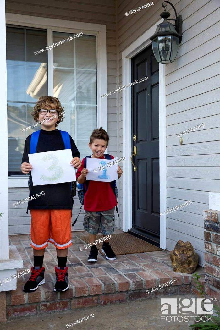 Stock Photo: Portrait of two brothers holding up pieces of paper with 3 & 1.