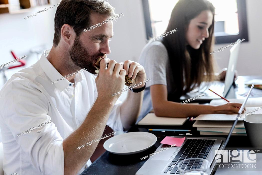 Stock Photo: Man eating and woman using laptop at home.
