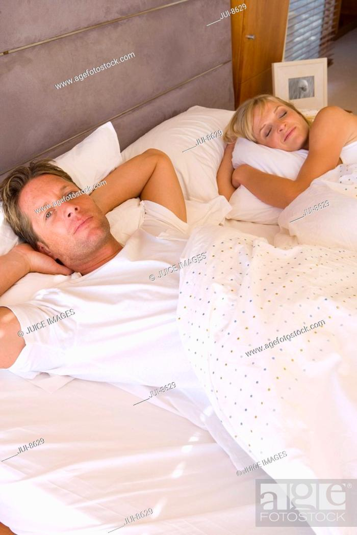 Stock Photo: Young couple lying in bed beneath covers, portrait, elevated view.