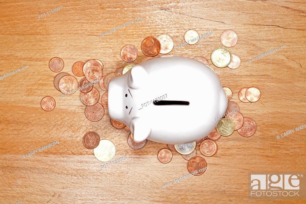 Stock Photo: A piggy bank on top of a pile of various European Union coins.