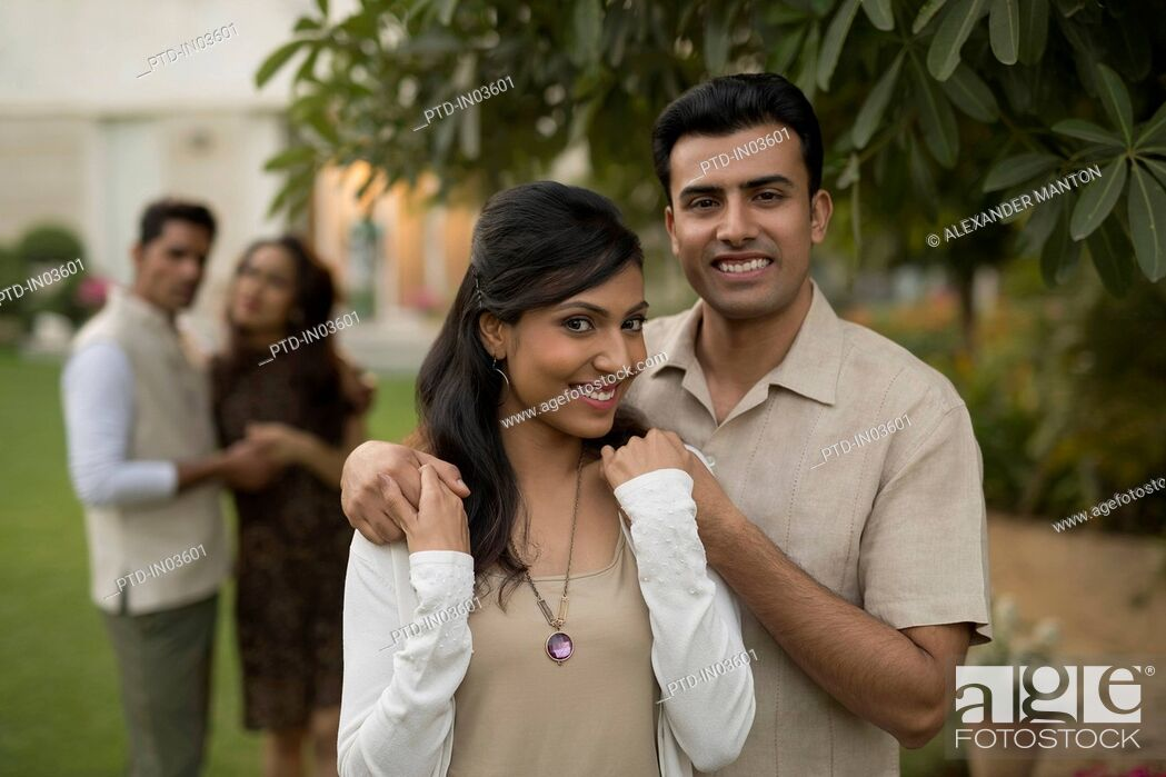 Stock Photo: Man with hands on woman's shoulder with friends in background.