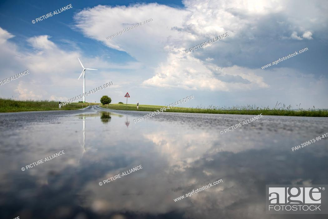 Stock Photo: 13 June 2020, Saxony, Waldenburg: The landscape is reflected in the wet country road after a rain shower. In the afternoon heavy thunderstorms are predicted for.